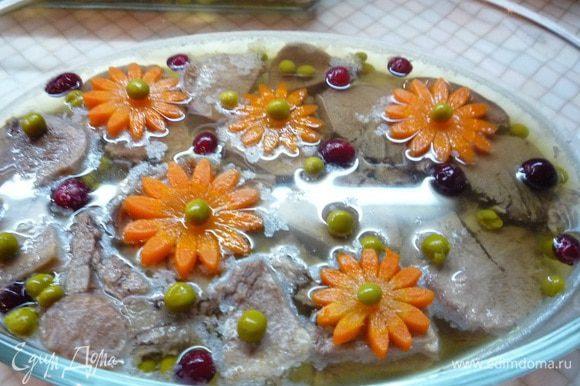 Украшаем заливное ягодами клюквы, зеленым горошком, по необходимости доливаем бульон и убираем на ночь в холодильник.