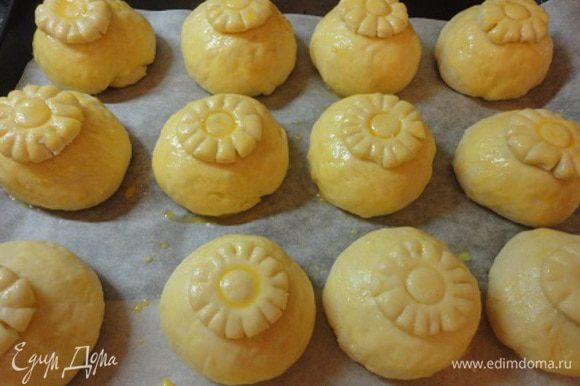 Подошедшие булочки смазываем желтком, укладываем цветочки и тоже смазываем желтком.