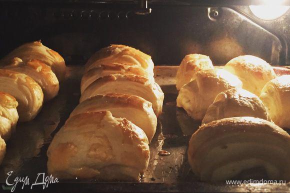 Получившиеся слойки нужно выложить на смазанный или застеленный пергаментом противень. Одно оставшееся яйцо взбить вилочкой в стакане и кистью смазать слойки. Выпекать на 180°C примерно 20-25 минут.
