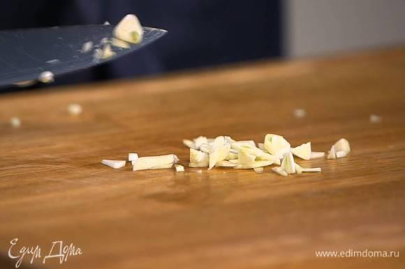 Чеснок почистить, мелко порубить, добавить в сковороду с луком и обжарить все вместе до слегка золотистого цвета.
