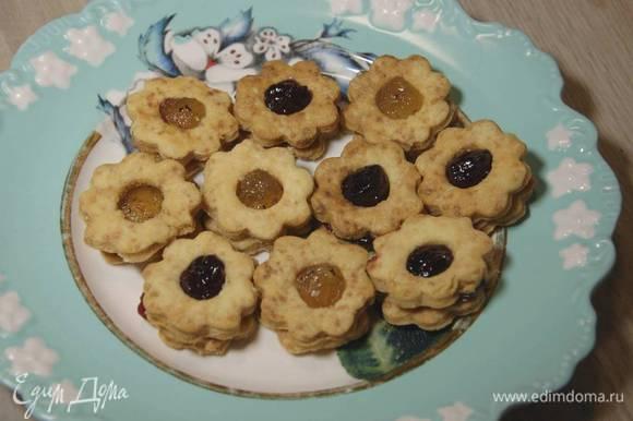 Печенье без отверстий смазать джемом и накрыть сверху печеньицами с отверстиями.