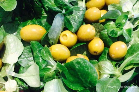 Добавить листья салата и оливки.