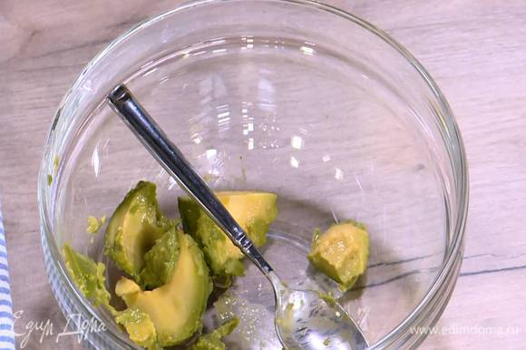Авокадо разрезать пополам и, удалив косточку, ложкой вынуть мякоть, полить ее соком лайма, а затем размять вилкой, так чтобы получились неравномерные кусочки.