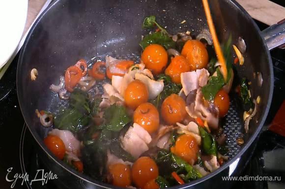 Бекон нарезать небольшими кусочками, добавить в сковороду с помидорами и шпинатом, перемешать и обжарить.