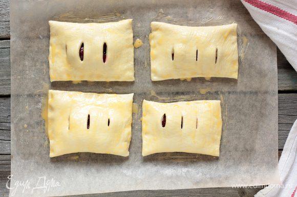 Противень выстелить бумагой для выпечки, смазать сливочным маслом, и выложить вишневые слойки, смазать их взбитым яйцом с молоком, присыпьте сахаром и уберите в разогретую до 190°C духовку на 20-25 минут или до появления румяной корочки.