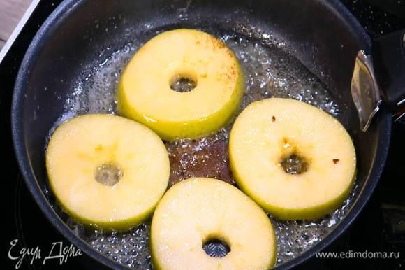 Разогреть в сковороде растительное и сливочное масло, выложить яблочные кружки, посыпать сахаром и обжарить с двух сторон, так чтобы яблоко получилось мягким, но не развалилось, затем переложить в другую посуду.