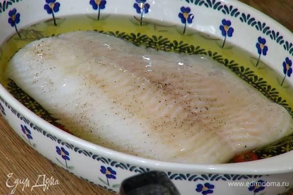 На дно жаропрочной керамической формы выложить перец чили, чеснок, посыпать розмарином, посолить, поперчить, сверху уложить палтус и залить все горячим оливковым маслом, так чтобы филе было покрыто.