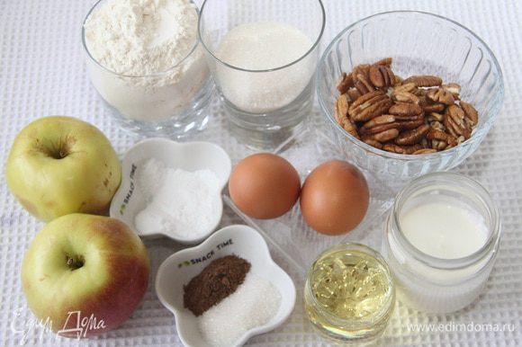 Понадобятся 2 яблока, 250 г муки, 100 г сахара, 2 ч.л. разрыхлителя, 1/2 ч. л. соды, 1/2 ч. л. соли, 100 г йогурта, 60 мл растительного масла, щепотка ванилина, 2 яйца, а также 50 г орехов (пекан или грецких), для сахарной коричной корочки 1 ст.л. сахара и 1 ч.л. корицы.