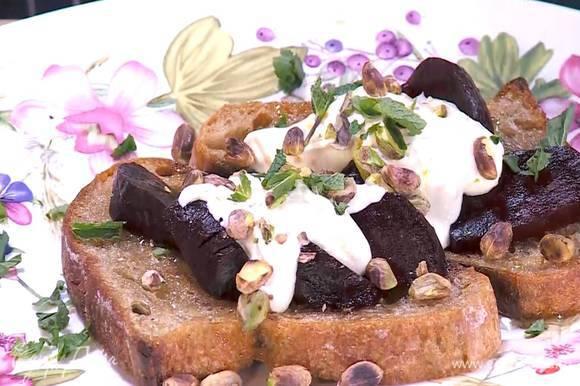 Обжаренный хлеб полить медом, выложить свеклу, смазать заправкой, посыпать фисташками и листьями мяты, порванной руками.