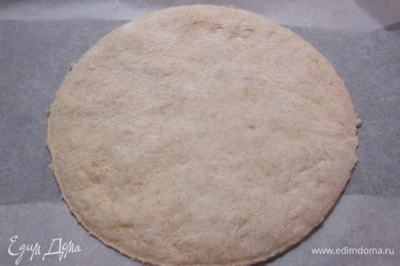 Тесто разделить на 2 равные части. Одну часть раскатать в круг диаметром 25 см, выложить на противень, выстланный бумагой для выпечки.