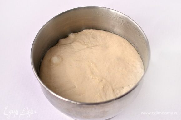 Емкость (смазать растительным маслом) с тестом накрыть пленкой, поставить в холодильник на 10 часов. Через 2 часа тесто обмять (в этой же емкости), как бы складывая его в конверт. Спустя 10 часов тесто достать из холодильника, дать ему согреться в течении 2 часов. Разделить тесто на 2 части, постараться сформировать по форме посуды, в которой будете выпекать. Руки смазать растительным маслом, т.к. тесто липковато. Я выпекала в эмалированных мисках. Тесту придала форму шара, уложила в смазанную растительным маслом миску. Дать тесту расстояться в теплом месте 60-70 минут. Обязательно накрыть сверху или фольгой, смазанной растительным маслом, или пленкой.