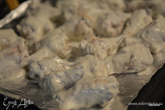 Достать крылышки из духовки. Воду слить. Приготовить противень с фольгой для выпечки. Смазать маслом. Куриные крылышки окунать в соус и выкладывать на противень. Поставить в горячую духовку на 25 мин.