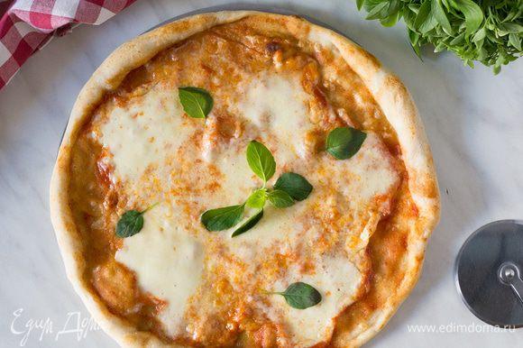 Отправьте пиццу в разогретую духовку на 6-8 минут. На готовую пиццу выложите листья базилика и подавайте. Приятного аппетита.