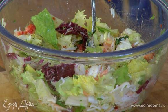 К крабовому мясу добавить листья салата, полить все заправкой, посолить, поперчить и перемешать.