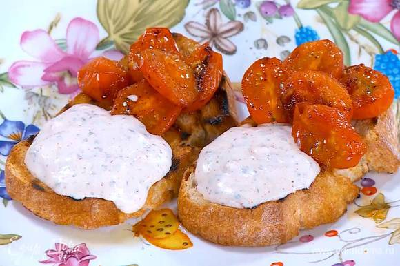 Подсушенный хлеб сбрызнуть оставшимся оливковым маслом, выложить обжаренные помидоры и йогуртовый крем, все посолить.