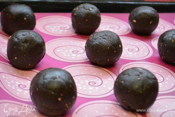 Из этого теста скатать небольшие шарики. Каждый шарик приплюснуть, на него положить кусочек шоколадки и завернуть края, формируя шарик.