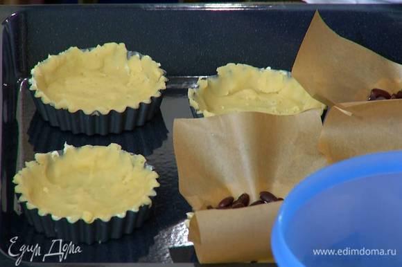 Из бумаги для выпечки вырезать круги или квадраты по количеству и размеру тарталеток, выложить бумагу на тесто и насыпать сверху фасоль.