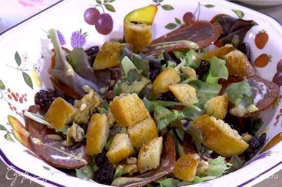 Грецкие орехи поломать руками на крупные кусочки и посыпать салат, сверху разложить вишню и крутоны.