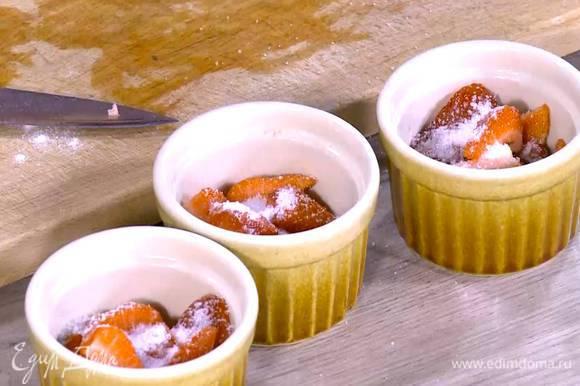 Клубнику разрезать на 4 части, выложить на дно небольших керамических форм и посыпать оставшимся сахаром и частью миндальных лепестков.