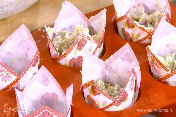 В небольшие формы поместить бумажные вкладыши и выложить тесто.