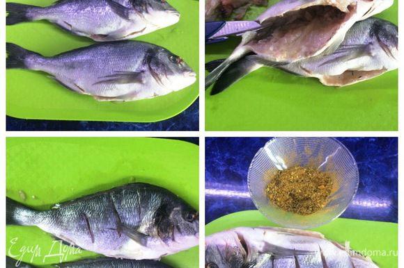 Начинаем с подготовки рыбы. Аккуратно чистим от чешуи. Плавники и хвост не отрезаем. Разрезаем брюхо острым ножом и потрошим. Удаляем жир, жабры, голову не отрезаем. С помощью кухонных ножниц и ножа вырезаем позвоночник и удаляем крупные кости. Делаем несколько надрезов наискосок, не очень глубоких. Это для того, чтобы рыба лучше просолилась и не скукожилась во время готовки. Подготовим смесь из специй, которой натрем рыбу. В ступке растираем специи. Несколько горошин черного перца, кориандра в зернах, сухих ароматных трав. Добавляем соли морской и 2-3 горошины душистого перца. После растирания получится ароматная смесь специй для рыбы. Посыпаем рыбу изнутри специями, и немного по шкуре. Оставляем рыбу полежать, пока будет жариться лук — минут 15-20.