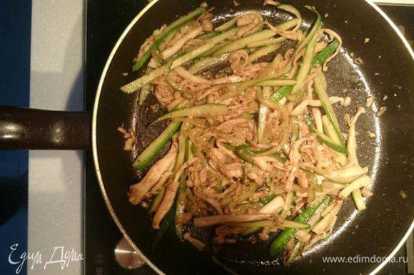 Мелко нарезать чеснок. Обжарить грибы с чесноком. Добавить огурцы, имбирь, поперчить, сбрызнуть соевым и рыбным соусами. Еще немного обжарить.