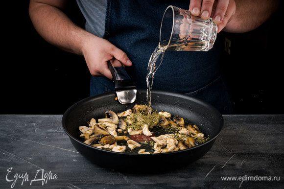 Куриной филе добавить к обжаренным грибам. Влить белое вино и дать алкоголю выпариться.
