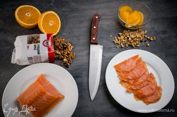 Полностью очистите от кожуры дольки апельсина, оставив лишь мякоть. Нарежьте сыр кубиками, а рыбу ломтиками.