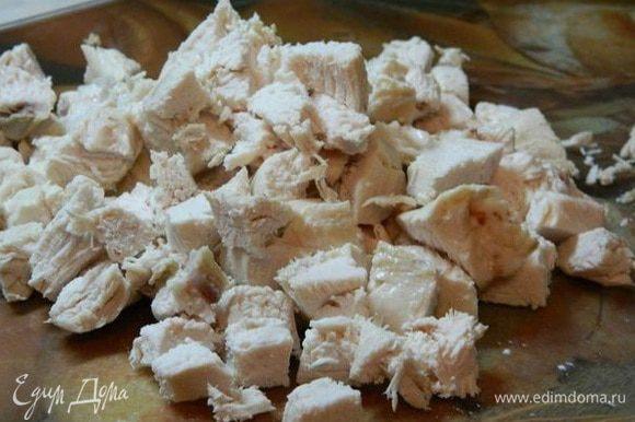 Отварную курицу отделить от костей и нарезать кубиками.