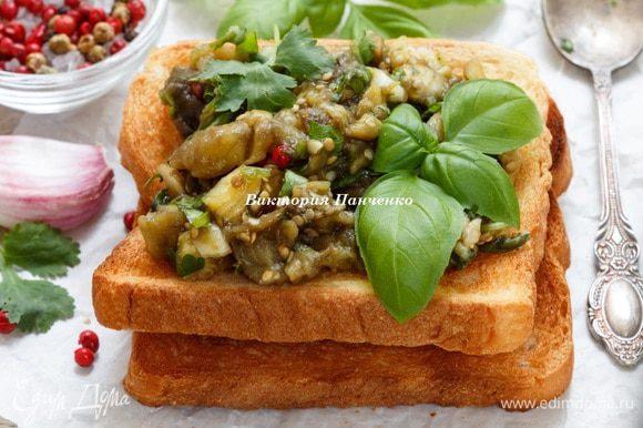 Хлеб подсушить в духовке или обжарить на сухой сковороде до румяной корочки. Выложить на тосты баклажаны, украсить базиликом. На одну порцию — 2 кусочка хлеба и один средний баклажан.