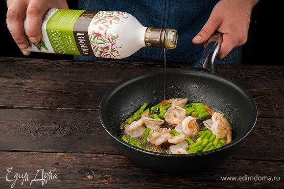 Разогреть в сковороде кунжутное масло и обжарить размороженные креветки почти до готовности, затем добавить спаржу и обжаривать все еще 3 — 4 минуты. Зеленый лук тонко порезать наискосок.
