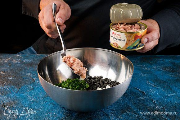 Смешиваем тунец, с маслинами и петрушкой и добавляем 2/3 заправки.