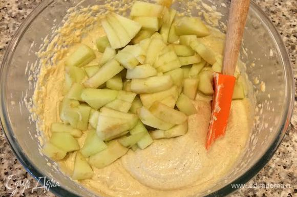 Добавить остальную муку, перемешать. Яблоки очистить и мелко нарезать, добавить в тесто и перемешать ложкой.