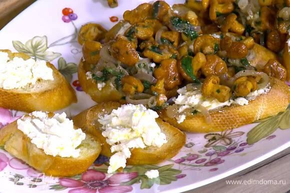 Поджаренный хлеб смазать лимонным сыром, сверху поместить лисички с луком и чесноком.