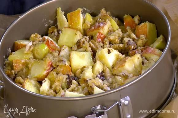 Дно разъемной формы для выпечки выстелить пищевой бумагой, равномерно выложить тесто, а сверху яблочно-ореховую начинку.