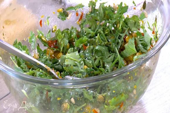 В заправку для салата выложить нут, подсолнечные и тыквенные семечки, руколу, нарезанную зелень и все перемешать.
