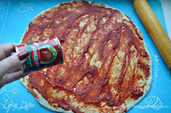 Раскатайте тесто в овал или прямоугольный пласт. Обильно смажьте томатной пастой «Помидорка» и сбрызните оливковым маслом.