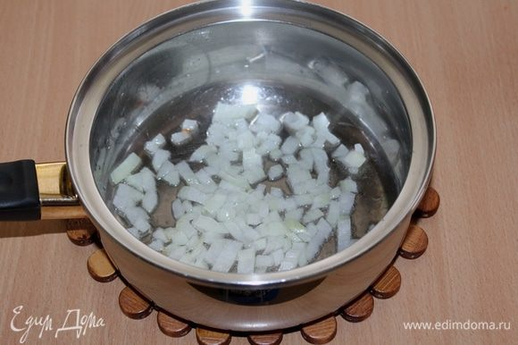 Разогреть в толстостенной кастрюле растительное масло и обжарить в нем до прозрачности мелко нарезанный лук.