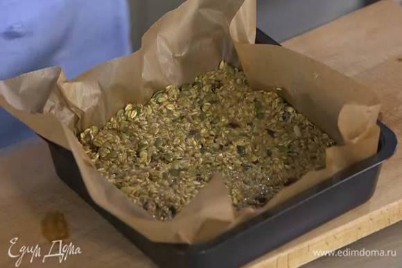 Небольшой противень с высокими бортами выстелить бумагой для выпечки, выложить овсяную массу и разровнять ее, слегка утрамбовав, так чтобы получился корж толщиной 1‒2 см.