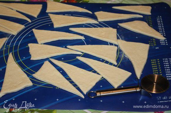 На рабочую поверхность просеиваем небольшое количество муки. Берем пласт слоеного дрожжевого теста и раскатываем в прямоугольный пласт. Визуально делим тесто пополам по ширине и делаем маленькие насечки. По длине делим тесто на четыре равные части, так же делаем насечки. Это нужно для того, чтобы тесто разделить на равные кусочки. Лучше всего пользоваться ножом для пиццы, чтобы не примять края теста. Разрезаем тесто на равные прямоугольники, каждый прямоугольник разрезаем по диагонали и получаем треугольники.