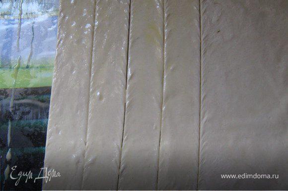 Из теста раскатать прямоугольник со стороной 25см, толщиной 3 мм. Разрезать его на полоски шириной 2,5 см и длиной 25 см. Растереть желток с водой. Смазать полоски.