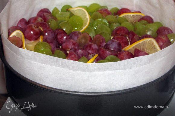 Виноград вымыть, разрезать на половинки и вытащить косточки. Выложить на бисквит виноград и тонкие ломтики лимона. Поставить в холодильник охлаждаться.