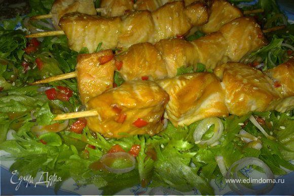 В маринад, где была рыба, добавит еще немного соевого соуса, тонко нарезать лук-шалот, салатные листья выложить на блюдо, посыпать луком-шалотом и полить маринадом. Сверху выложить шашлычки.