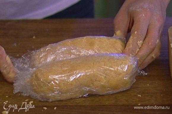 Предварительно размягченное сливочное масло и сыр добавить к муке и вымешать тесто, затем разделить его пополам, сформировать две колбаски диаметром 5–8 см, завернуть их в пищевую пленку и отправить в холодильник на 30 минут.
