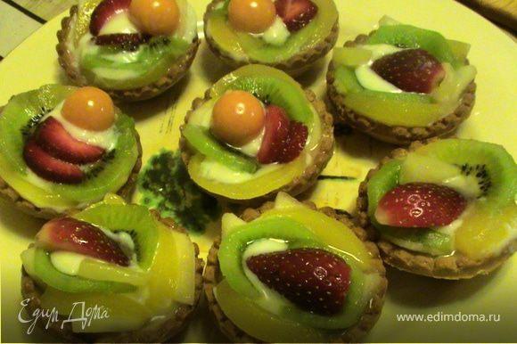 В песочные корзинки выложить заварной крем, затем фрукты и ягоды. Для того, чтобы фрукты не потемнели на них необходимо нанести разведенный пищевой желатин. Корзинки готовы. Приятного аппетита.