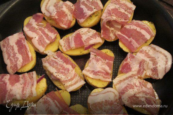 Картошку выложить на противень кожей вниз.сверху положить перышки лука и бекон, присыпать орегано и отправить в разогретую духовку (200 гр.) на 30-40 минут.