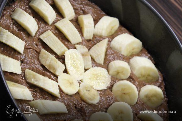 Выложить половину тесто в смазанную маслом форму. Выложить часть бананов и залить оставшимся тестом.Нарезанные кусочками бананы положить сверху, слегка их вдавливая.