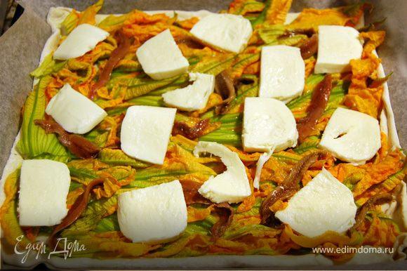 Порезать моцареллу на небольшие ломтики и уложить на пиццу, равномерно распределяя.