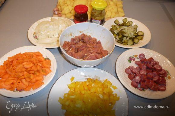 Мясо нарезаем порционными кусочками (2-3 см), маринуем в смеси горчицы (1 часть) и аджики (1/3 части). Немного солим, перчим. Оставляем минут на 20, пока подготавливаем остальные ингредиенты. Морковь режем колечками, лук - полукольцами (лук немного обжарить на растительном масле), болгарский перец - небольшими полосочками, картошку - кубиками, колбаски и корнишоны - кружочками. Сельдерей тонкими ломтиками. Чеснок делим на зубчики, но не чистим.
