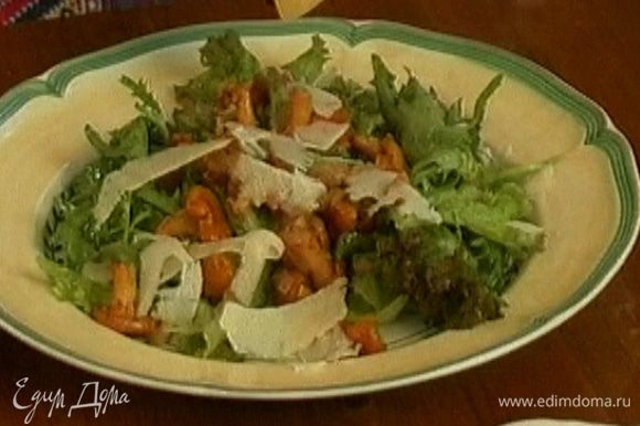 Выложить на листья салата лисички, сверху посыпать хлопьями сыра. Подавать салат теплым.